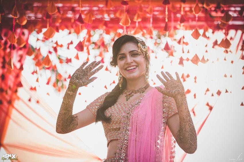 Pink floral lehenga Mehendi ceremony in Grand Hyatt Goa Cineyug Celebrations