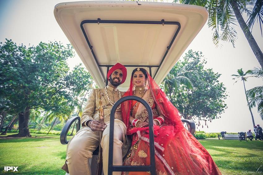 bride and groom red lehenga beautiful Sikh wedding in Grand Hyatt Goa couple ride in golf cart