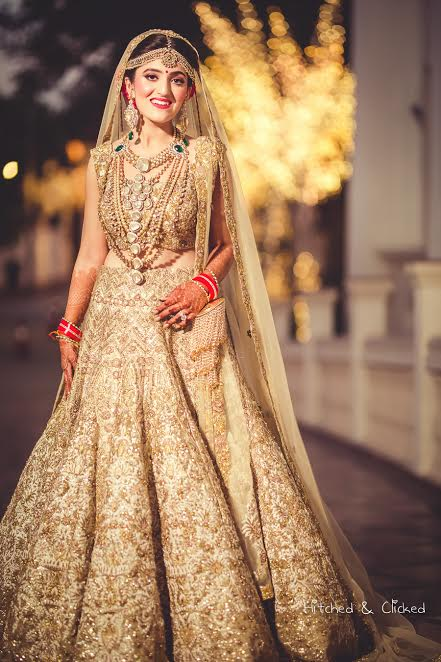 bride poses in a beautiful Golden beige lehenga by Harpreet and Rimple Narula