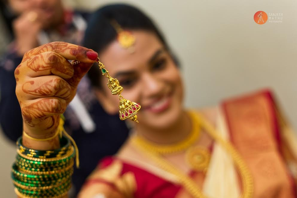 bride holds up her jhumka and smiles